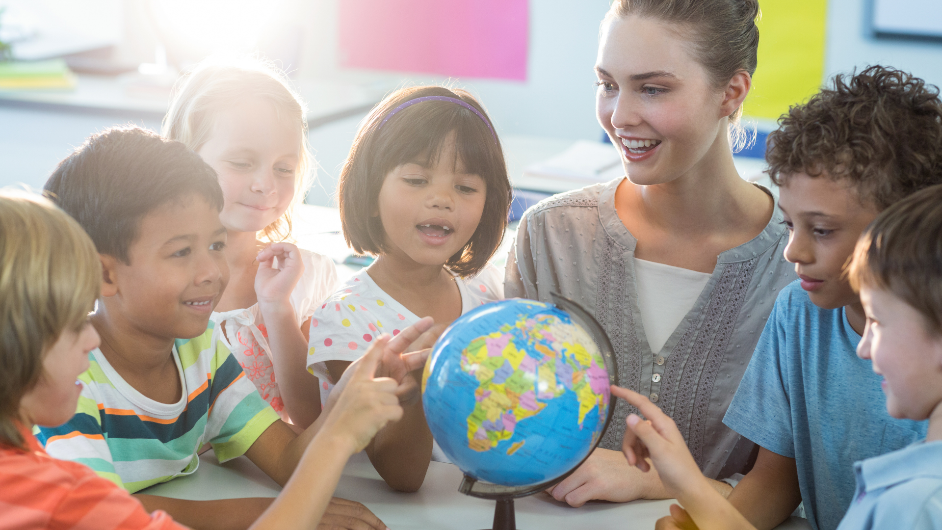 Image shows a teacher sitting with students while interacting with a globe.