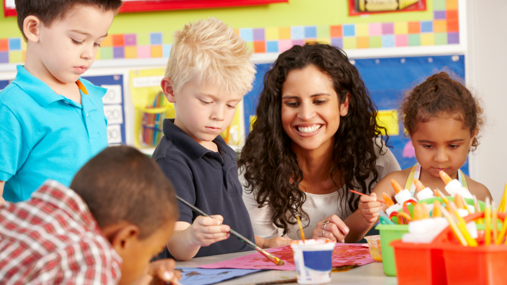 Image shows a teacher sitting with students during a classroom activity.