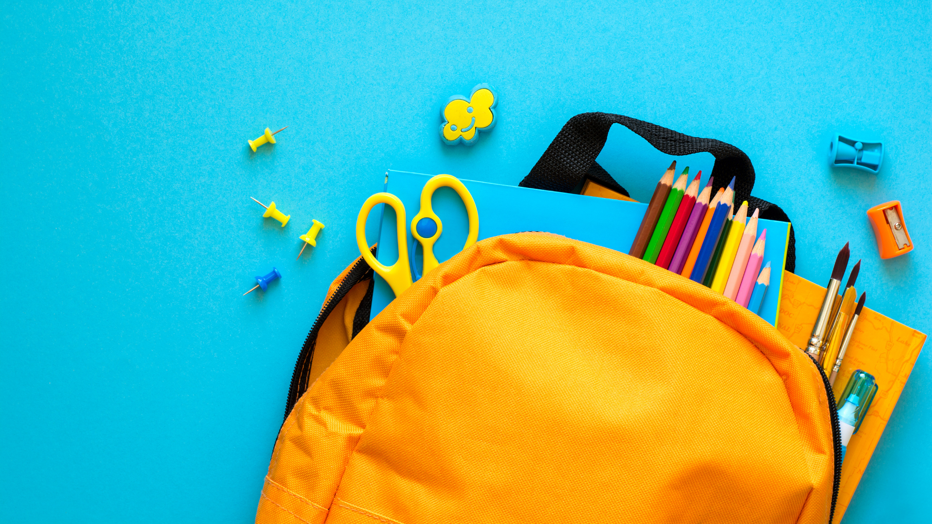 Image shows an open backpack with school supplies spilling out.