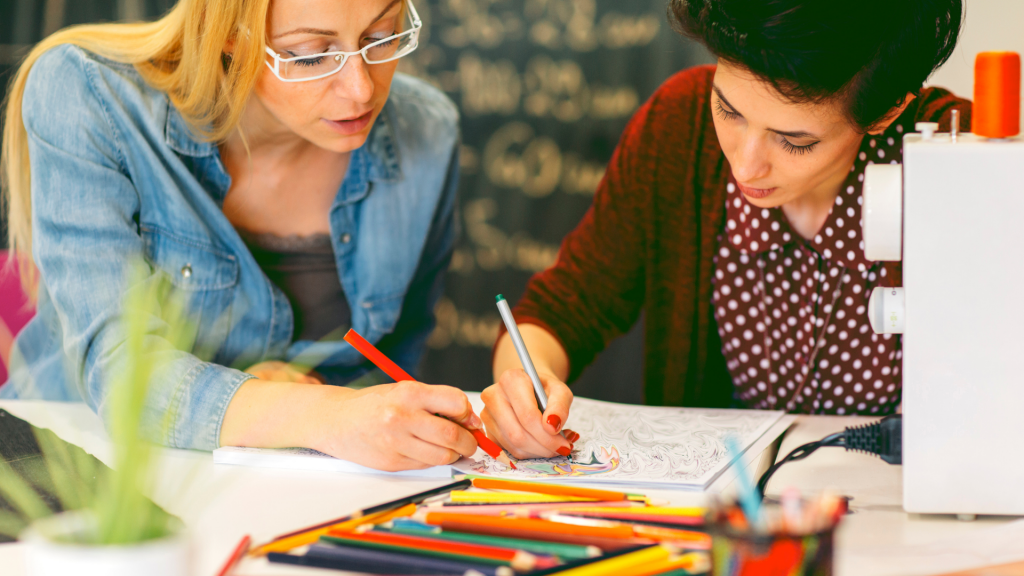 Image shows two adults coloring together.