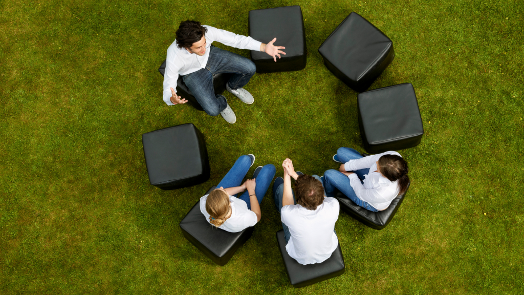 Image shows a birds eye view of adults sitting in a circle talking.