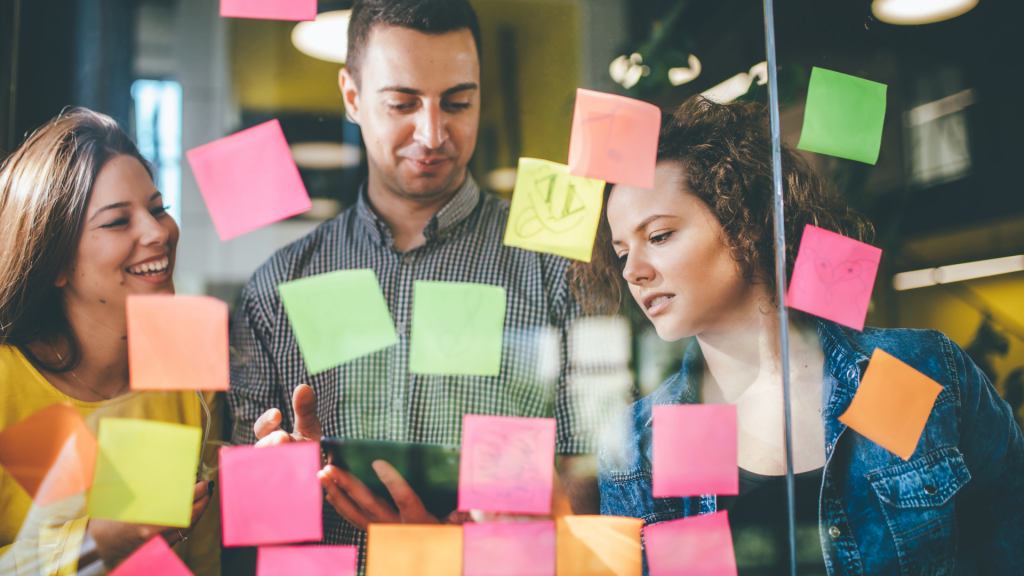 Image shows adults working on sticky notes together.