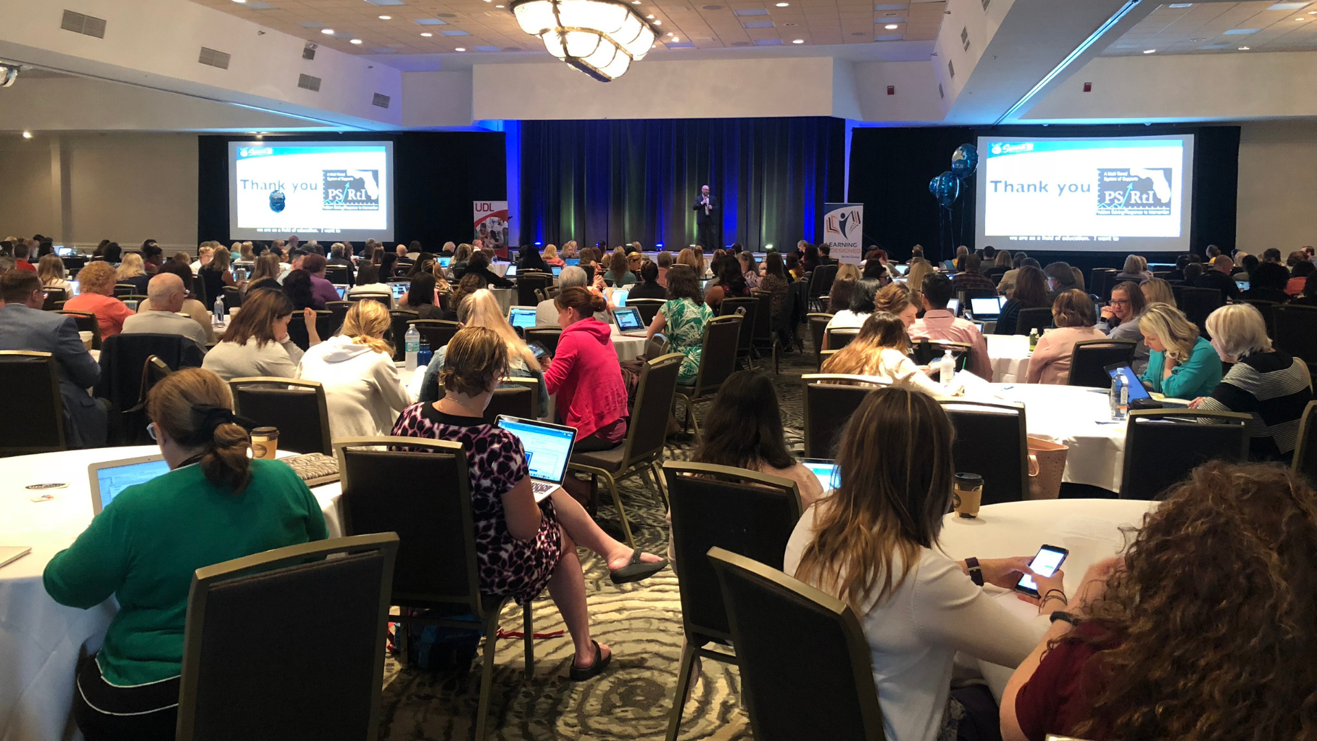 Image shows 2018 Summit attendees listening to Dr. James Basham.