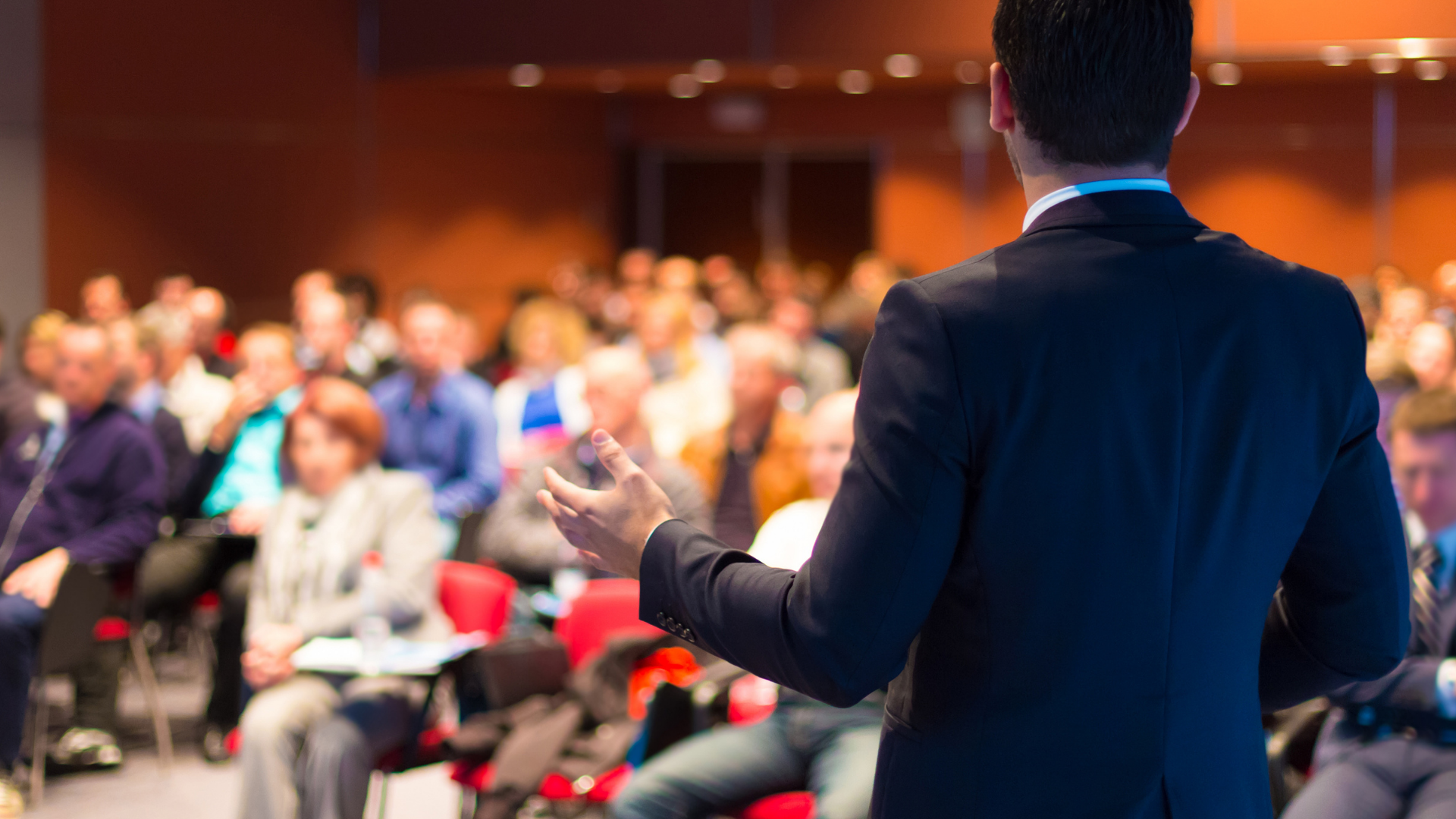 Image shows a conference presenter looking out over conference attendees.