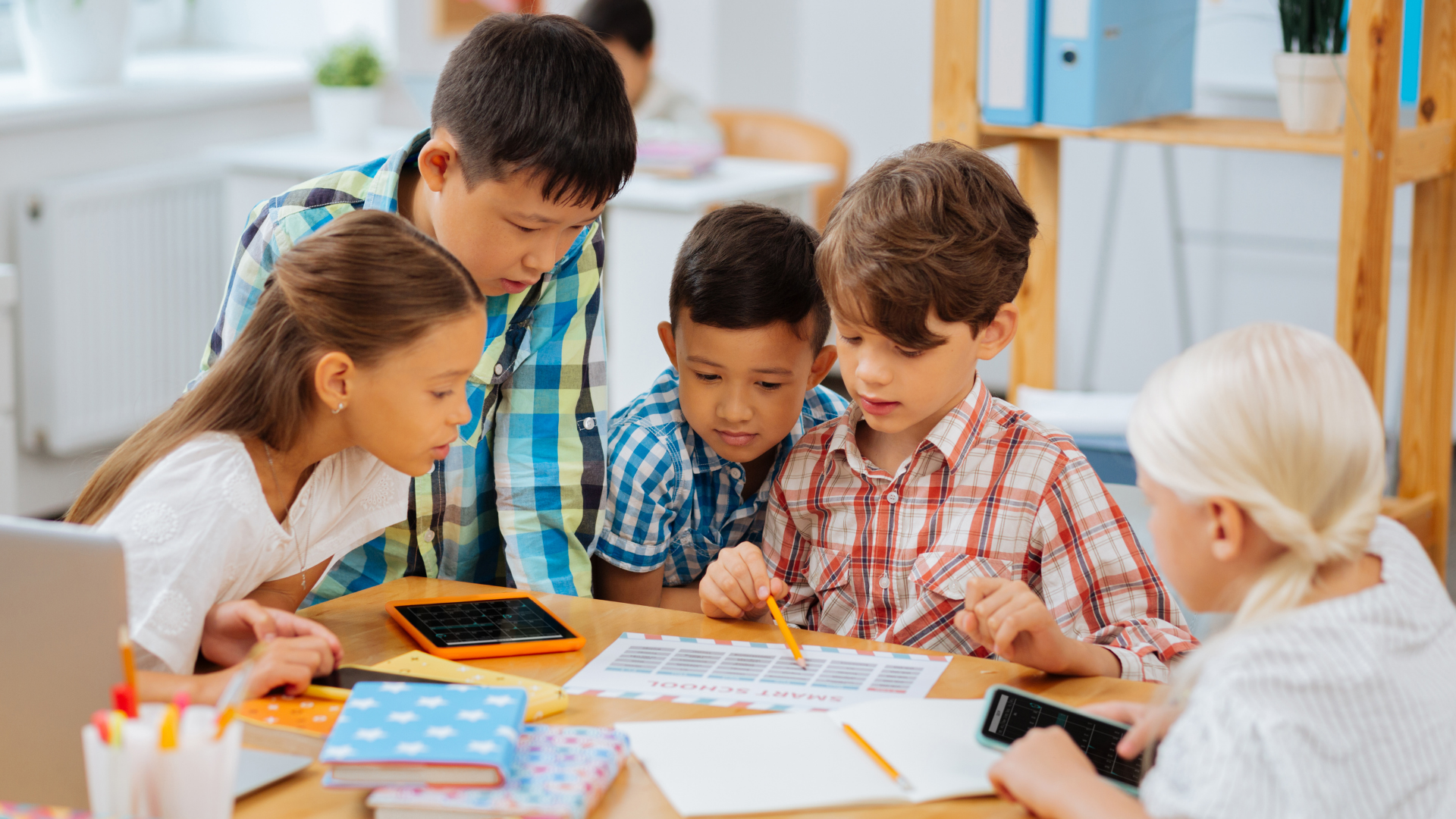 Image shows students working together around a classroom table.