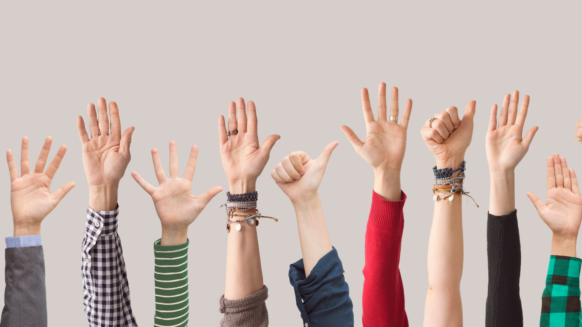 Image shows various raised hands.